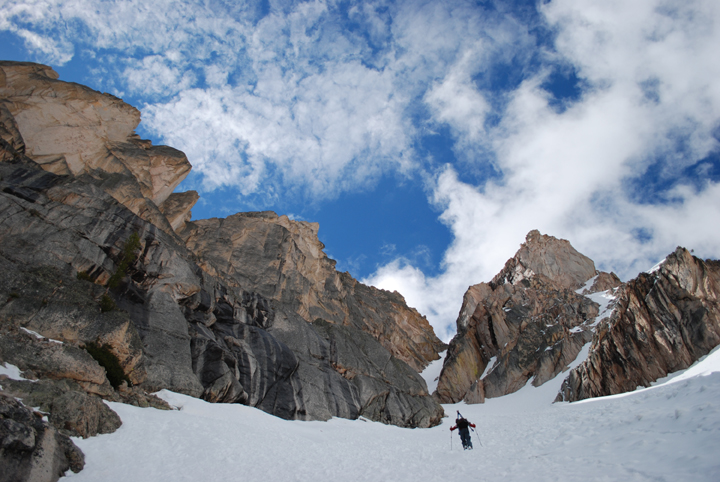 A skier is dwarfed by the huge rock walls of a couloir in the Sawtooth Wilderness.